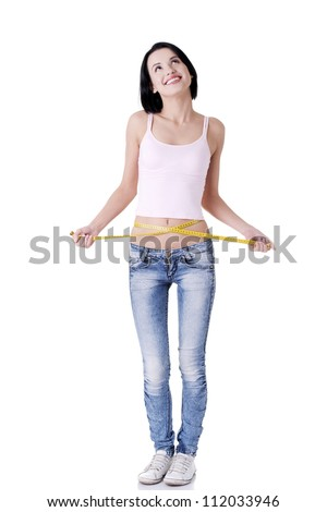 Happy young woman measuring her waist - stock photo