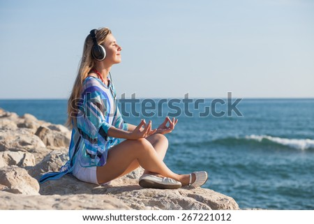 Happy young woman meditating at seacoast  - stock photo