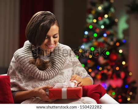 Happy young woman near christmas tree with present box - stock photo