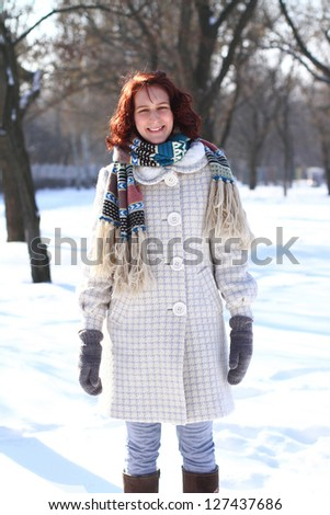 Happy young woman on a background of a winter park - stock photo