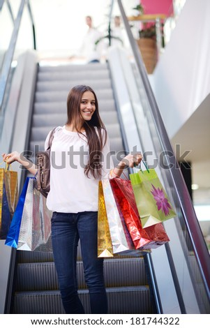 Happy young woman on escalators in a shopping mall with colorful fashion gift  bags