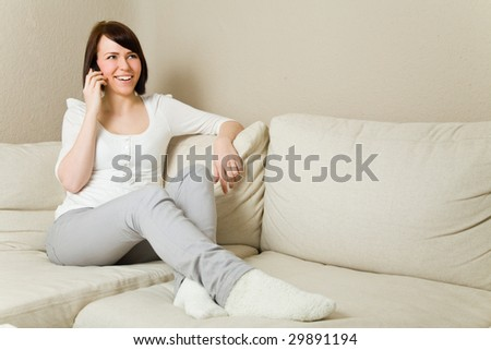 Happy young woman on her mobile phone in the living room - stock photo