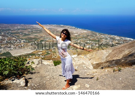 Happy young woman on holidays on the sea, top view on Santorini island - stock photo