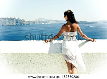 Happy young woman on holidays, Santorini Thira town  - stock photo