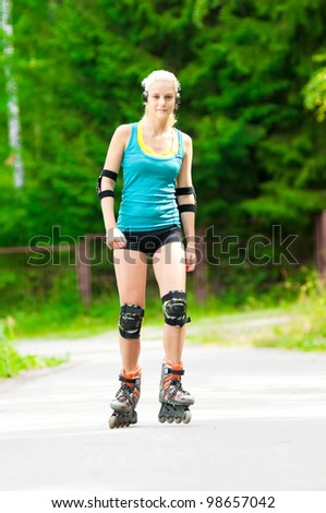 happy young woman on roller skates in the park - stock photo