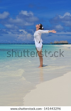 happy young woman on summer vacation on beautiful tropical beach have fun and relax - stock photo