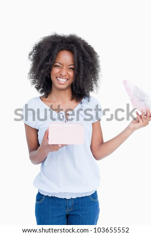 Happy young woman opening a present against a white background