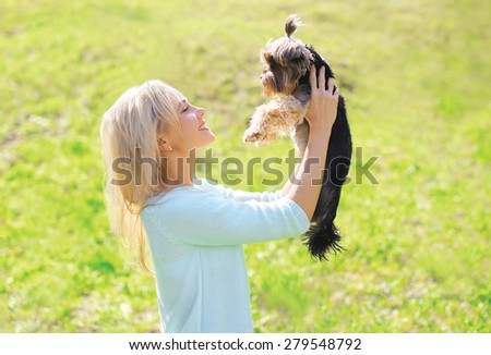 Happy young woman owner with yorkshire terrier dog in sunny park - stock photo