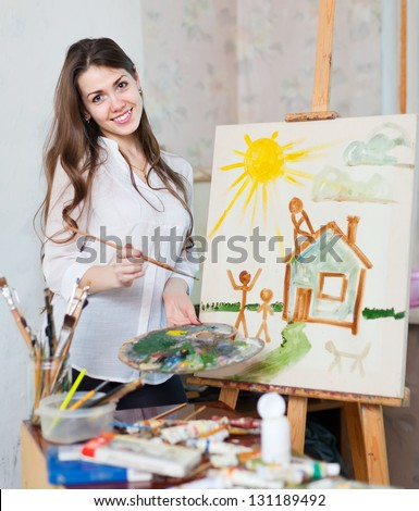 Happy young woman paints home  in workshop - stock photo