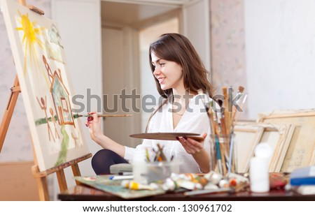 Happy young woman paints landscape on canvas in workshop - stock photo