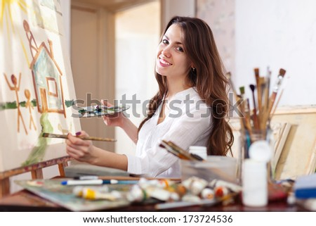 Happy young woman paints  on canvas in workshop - stock photo