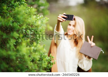 Happy young woman photographing herself using her mobile phone. Caucasian female talking selfie with her smart phone at park. - stock photo