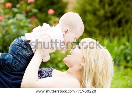 Happy young woman playing with baby boy in spring flowery garden. Nature blurred background - stock photo