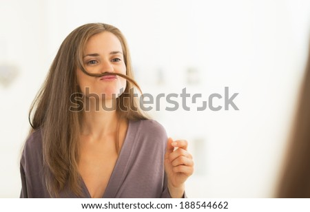 Happy young woman playing with hair - stock photo