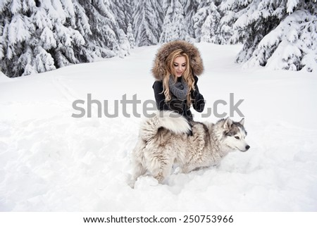 Happy young woman playing with siberian husky dogs in winter forest  - stock photo