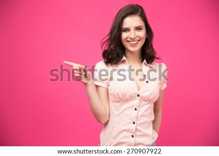 Happy young woman pointing finger away over pink background and looking at camera - stock photo