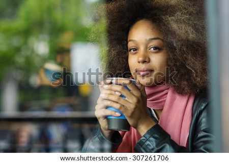 Happy young woman portrait drinking coffee inside a cafe. Image shot through a window. - stock photo