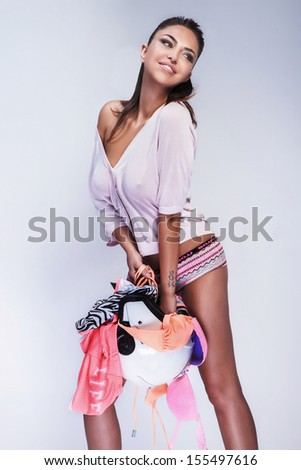 Happy young woman posing with a lot of clothes, looking away. - stock photo