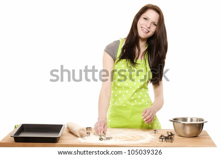 happy young woman pressing christmas molds in dough with white background - stock photo