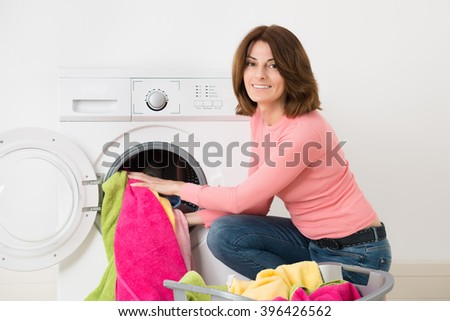 Happy Young Woman Putting Clothes Into Washing Machine