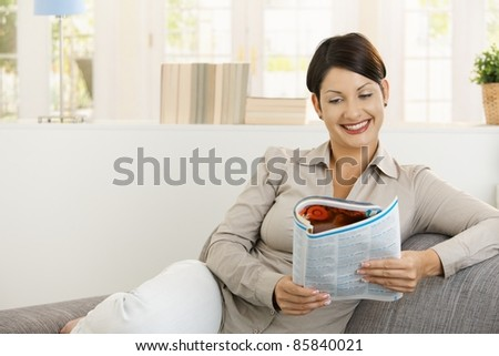 Happy young woman reading newspaper on sofa at home, smiling.? - stock photo