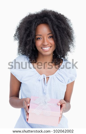 Happy young woman receiving a birthday gift against a white background