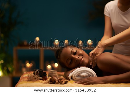 Happy young woman receiving relaxing back massage