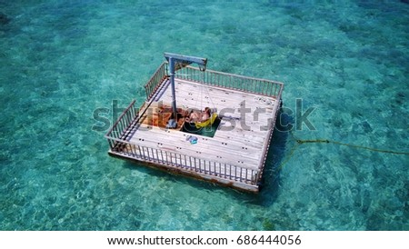 Happy young woman relaxing in pontoon middle of blue aqua sea background in summer Maldives