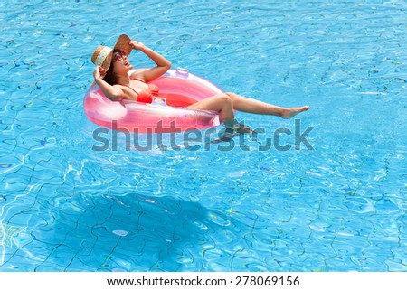 happy Young woman relaxing in swimming pool - stock photo