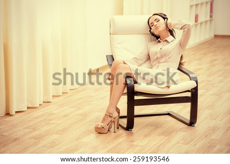 Happy young woman resting at home listening to music in headphones. - stock photo