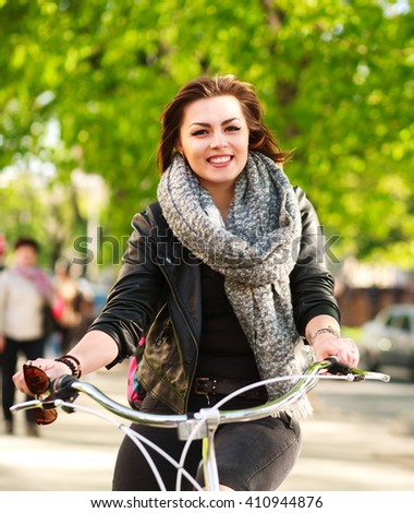 Happy young woman riding a bicycle in the green city park - stock photo