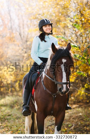 Happy Young woman riding a brown horse