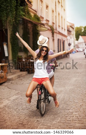 Happy young woman riding on bicycle with her boyfriend - stock photo
