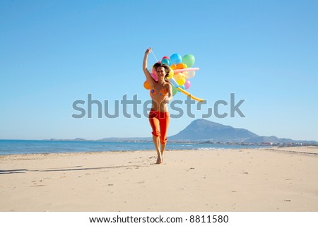 happy young woman running on the beach with different colored balloons