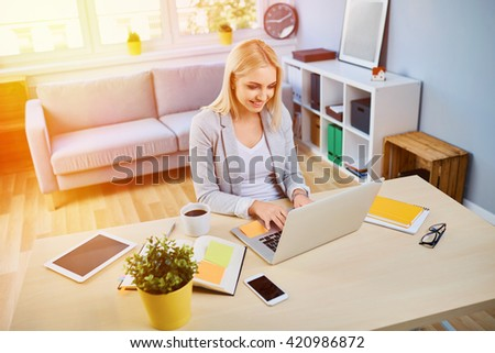 Happy young woman running small business from home office, working on laptop - stock photo