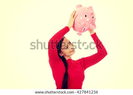 Happy young woman shaking piggybank - stock photo