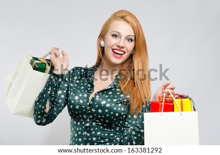 Happy young woman shopping for the holidays. Girl with many shopping bags and gifts. - stock photo