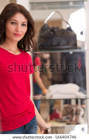 Happy young woman shopping in boutique store - standing near glasscase