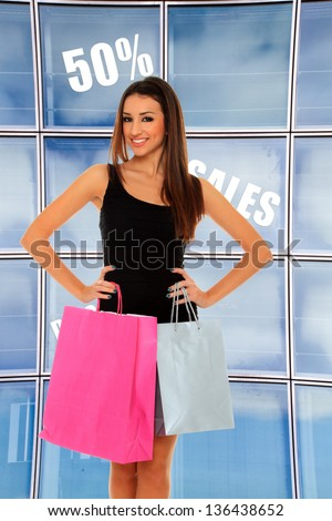 Happy young woman shopping in front of the store - stock photo