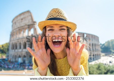 Happy young woman shouting through megaphone shaped hands in front of colosseum in rome, italy - stock photo