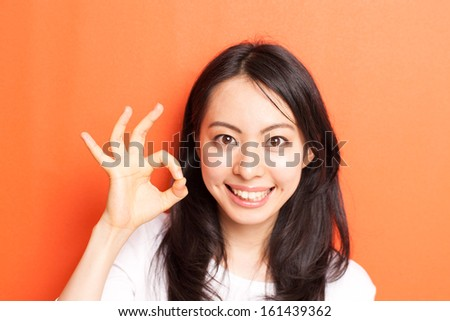 happy young woman showing OK gesture against orange background - stock photo