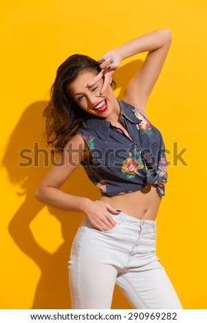 Happy  young woman showing peace hand sign on her face. Three quarter length studio shot on yellow background. - stock photo
