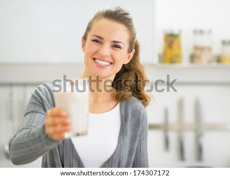 Happy young woman showing smoothie - stock photo