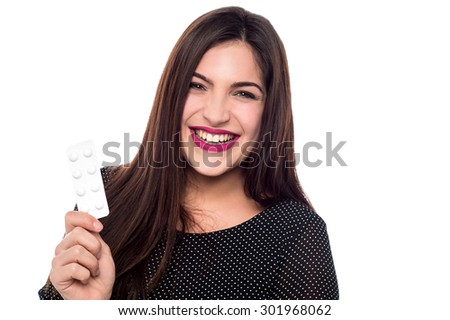 Happy young woman showing strip of pills - stock photo