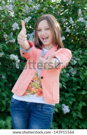 happy young woman showing thumbs up on the summer outdoors background - stock photo