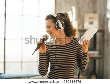 Happy young woman singing karaoke in loft apartment - stock photo