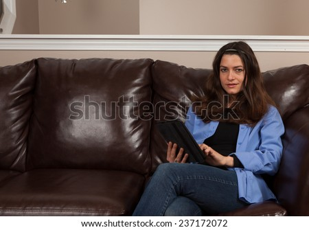 Happy young woman sitting alone on a couch with a tablet on a brown leather couch with room for copy above - stock photo