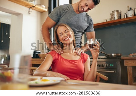 Happy young woman sitting at breakfast tablet holding cup of coffee getting a shoulder massage from her boyfriend. Young couple in morning with boyfriend rubbing girlfriends shoulders in kitchen. - stock photo
