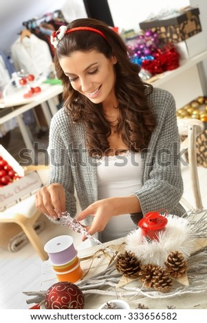 Happy young woman sitting at table, making hand made christmas decoration. - stock photo