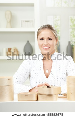 Happy young woman sitting at table with boxes on it, smiling.
